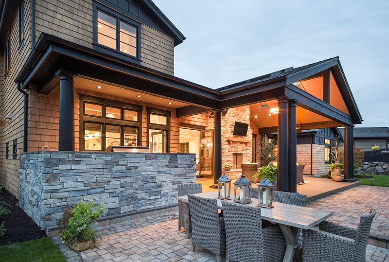 Angled rear view with covered outdoor living and an open patio filled with a rectangular dining table and wicker chairs.