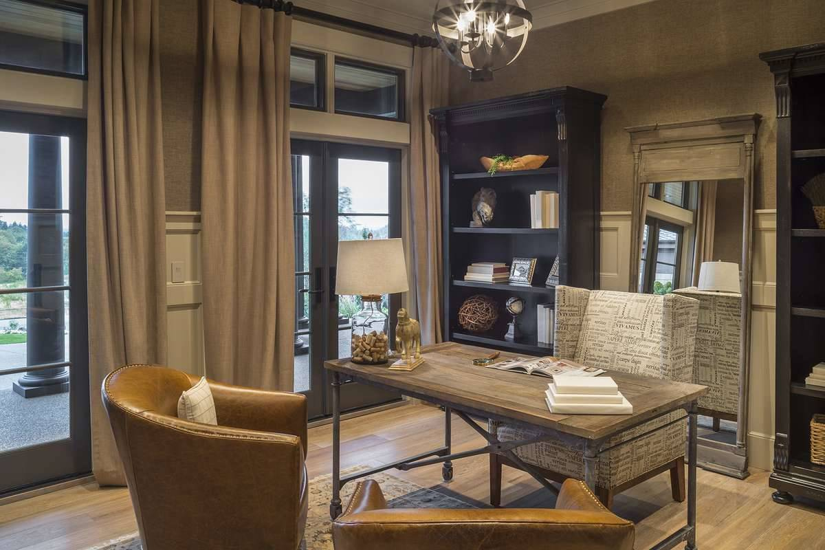 The study is filled with wingback and leather round back chairs along with a wooden desk that matches the full-length mirror.