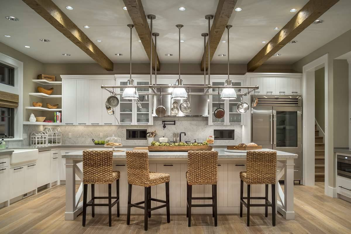 The kitchen has a beamed ceiling mounted with chrome pot racks and glass dome pendants that hang over the breakfast bar.