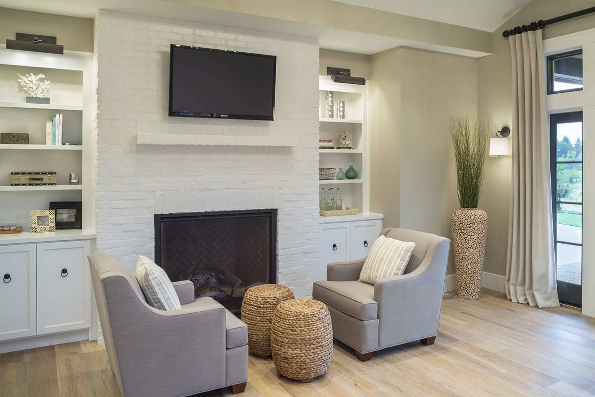 A sitting area by the fireplace flanked by white built-ins.
