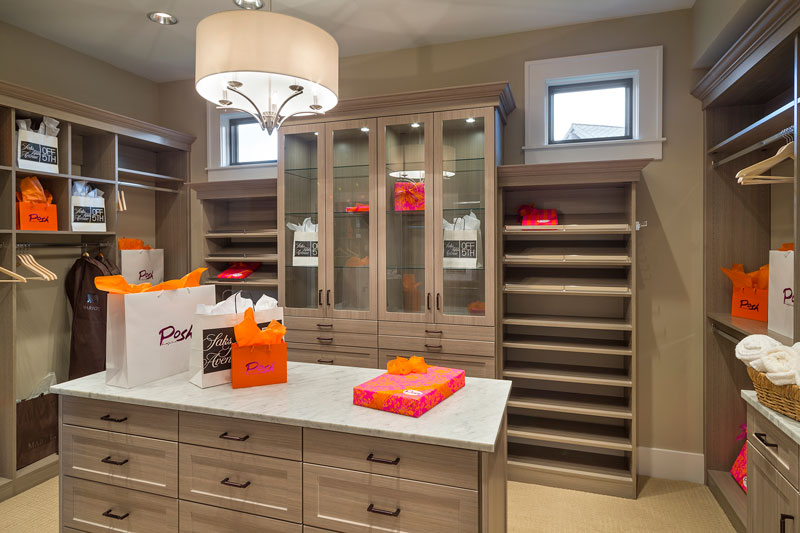 Walk-in closet with light wood shelvings and cabinet along with an island lit by a drum chandelier.