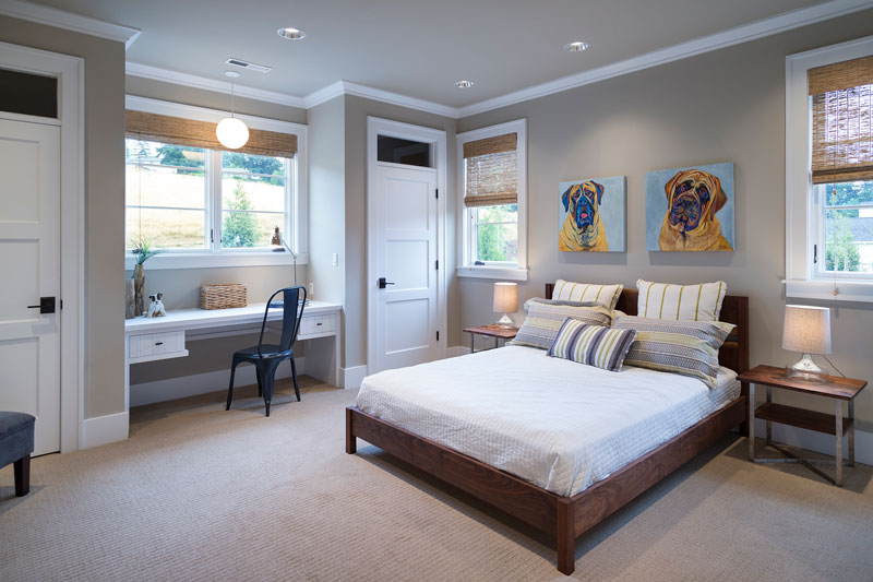 This bedroom has a white desk and a wooden bed situated under the dog artworks.