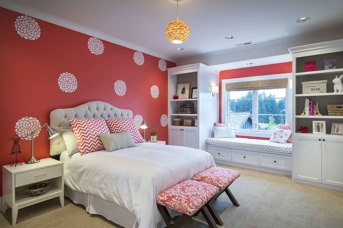 Bedroom with a window seat and a cozy tufted bed placed against the red patterned wallpaper.