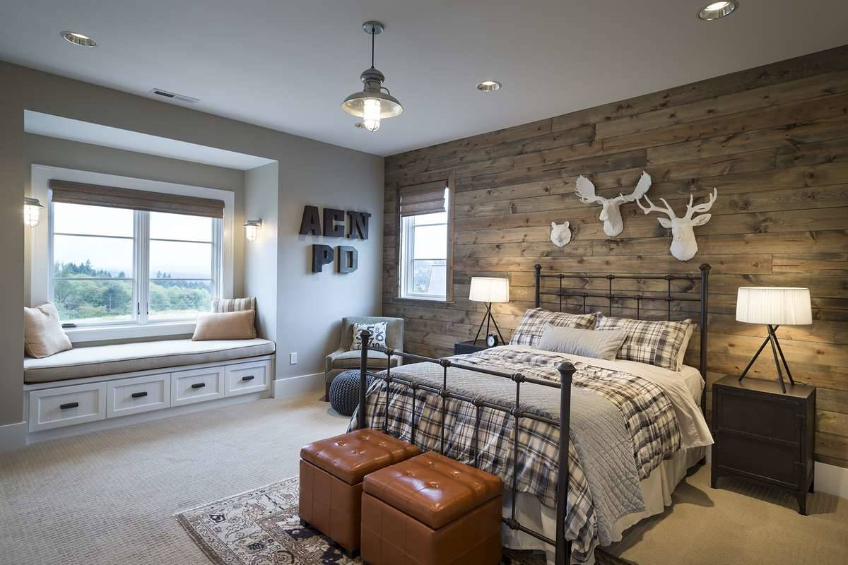 Another bedroom with a window seat and an accent wall clad in rustic wood planks.