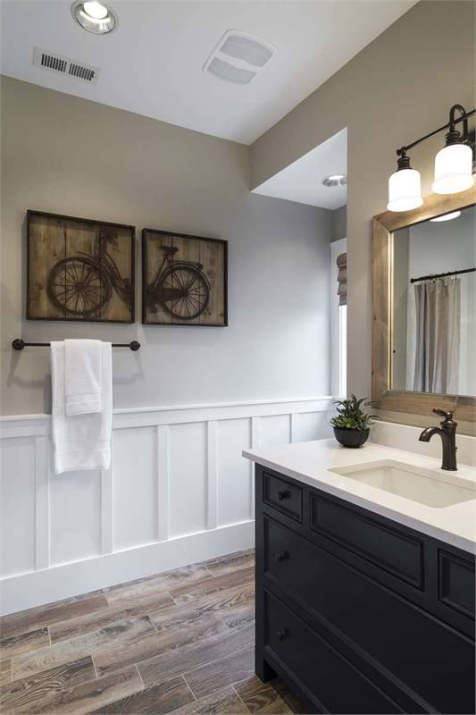 Powder room with wide plank flooring and light gray walls adorned with white wainscoting and multi-panel artworks.