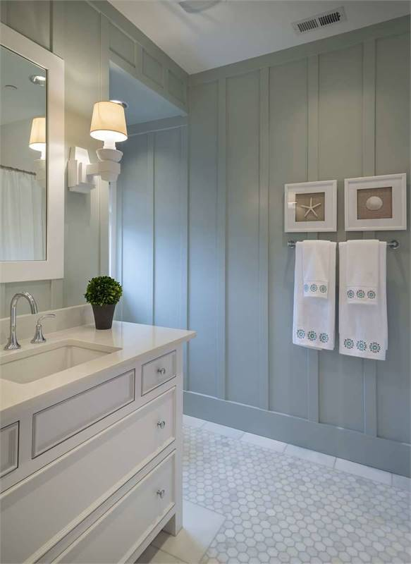This powder room has hex tile flooring and light blue beadboard walls mounted with a towel rack and small white framed artworks.