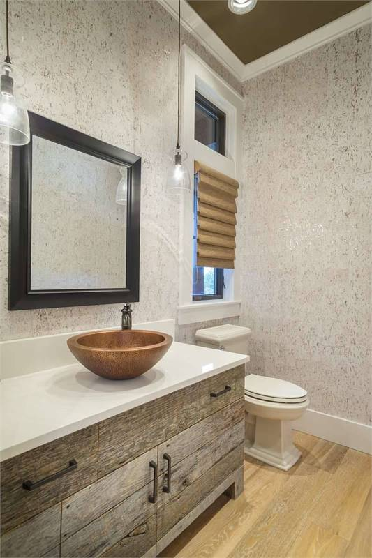 This bathroom is equipped with a toilet and a vessel sink vanity illuminated by glass dome pendants.