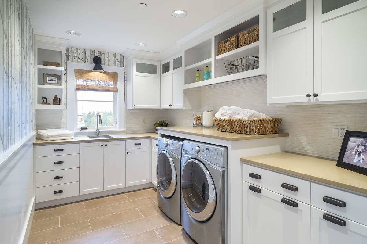 Laundry room with white cabinets, stainless steel appliances, and a small window dressed in wicker roman shade.