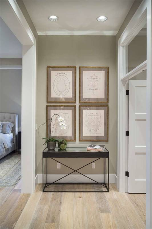 This hallway is adorned with framed artworks fixed above the metal console table.