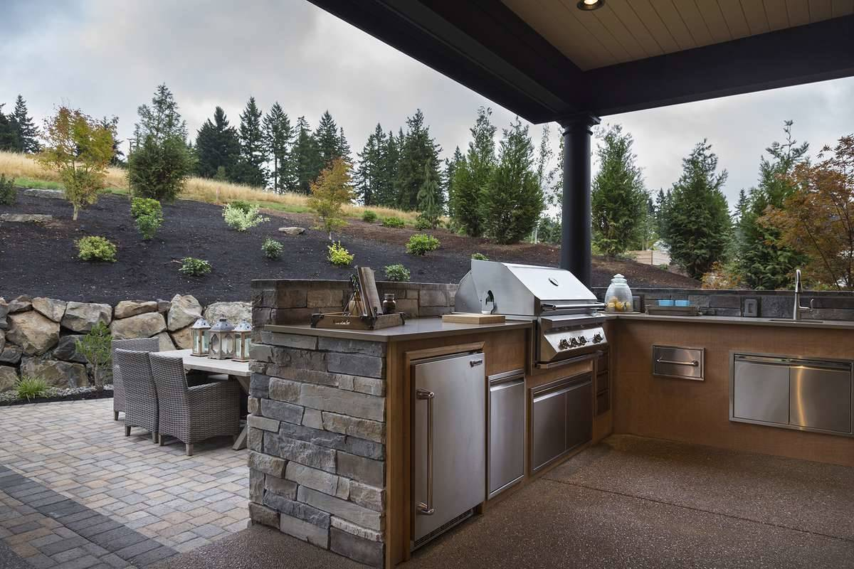 Outdoor kitchen with a wraparound bar fitted with stainless steel appliances and undermount sink.