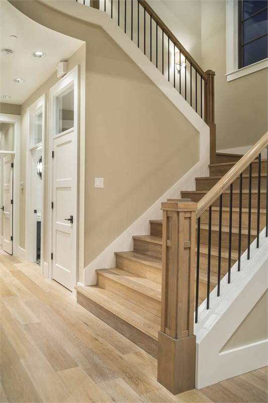 The staircase is composed of wrought iron spindles, a carved newel post, and wooden steps that blend in with the wide plank flooring.