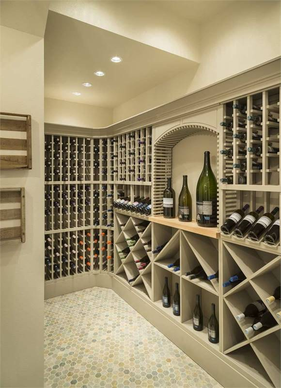 The wine cell has hex tile flooring along with column and crisscross shelvings that blend in with the taupe walls.