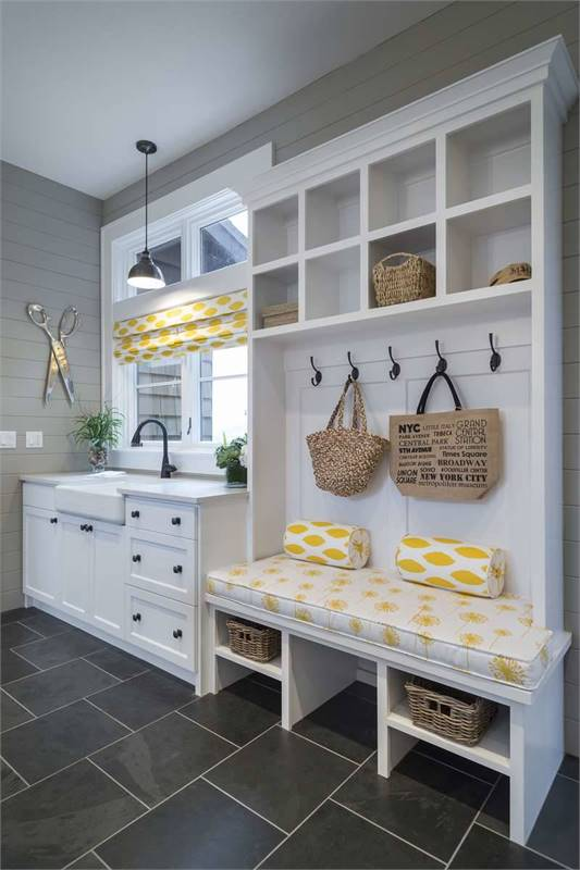 Mudroom with built-in bench, white cabinets, and a farmhouse sink paired with a gooseneck faucet.