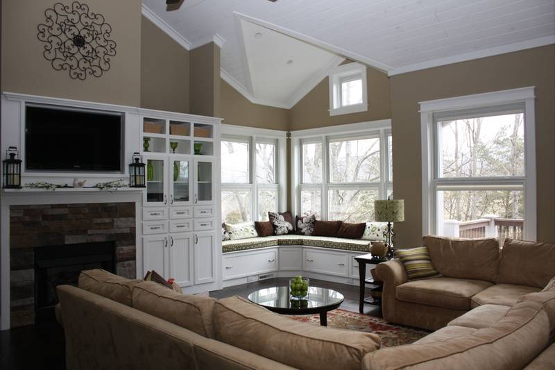 The living room has a u-shaped beige sectional and a round coffee table facing the TV and fireplace.