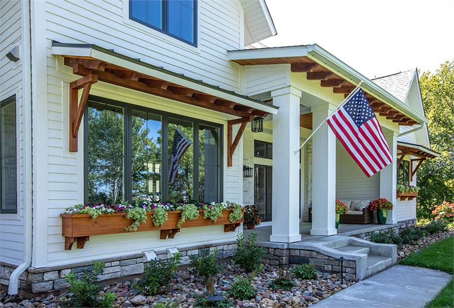 Decorative exterior columns adorned with a flag support the front porch.