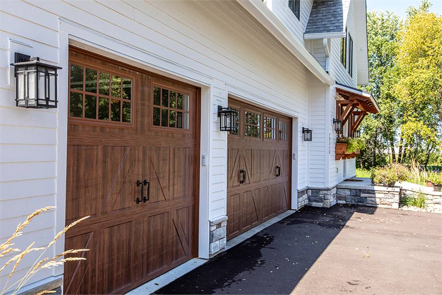 A close-up look at the garage with large wooden doors illuminated with outdoor sconces.