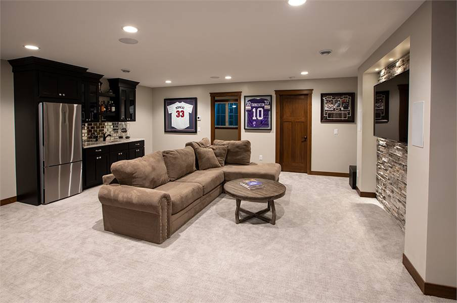 Family room with an L-shaped sectional and a round coffee table facing the TV that's fixed against the brick accent wall.