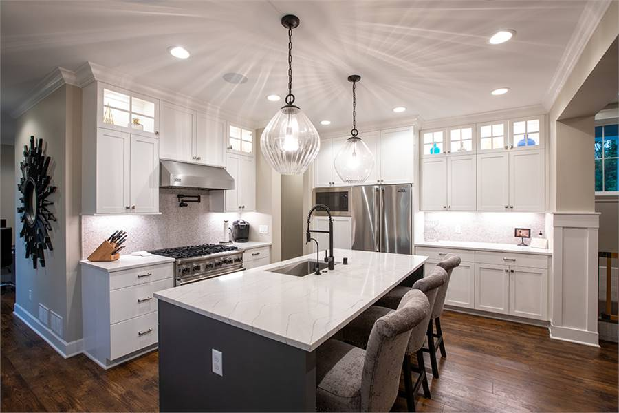 The kitchen is equipped with stainless steel appliances, white cabinets, and an undermount sink fitted on the marble top island.