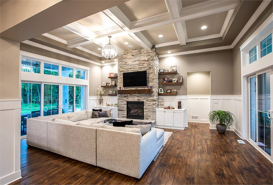 The living room has natural hardwood flooring and a stunning coffered ceiling mounted with recessed lights and a round chandelier.