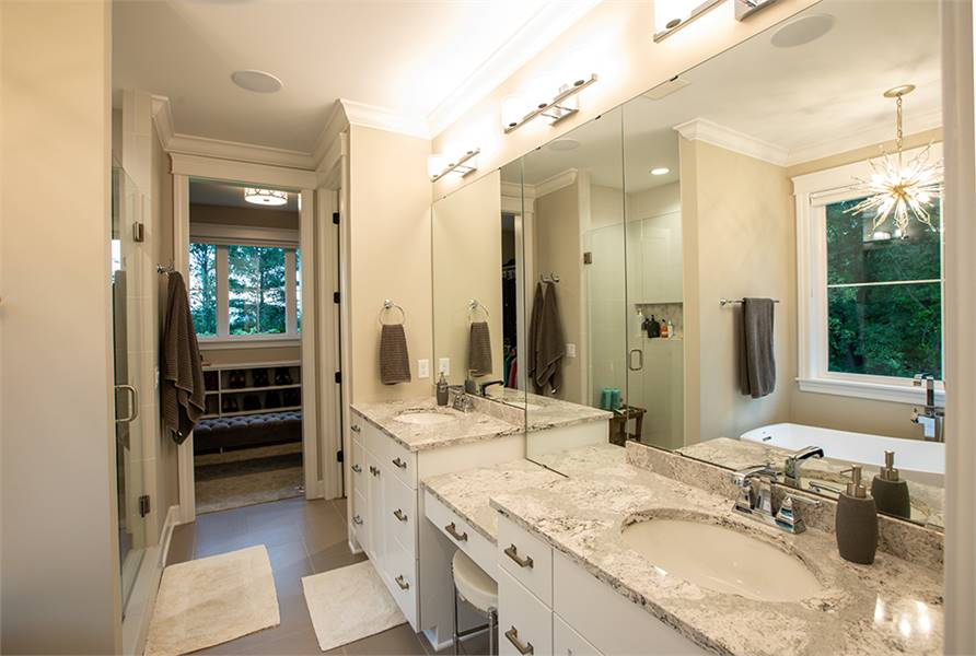 The primary bathroom offers a shower and a large dual sink vanity. There's a door on the side that opens to the walk-in closet.
