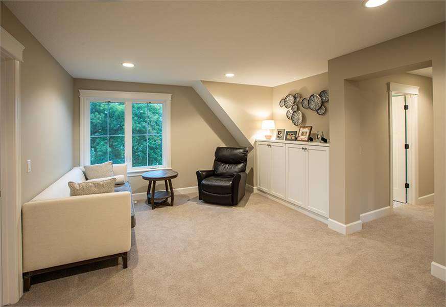 The bonus room is filled with a beige sofa, a small round table, a black leather recliner, and a white built-in cabinet topped with framed photos.