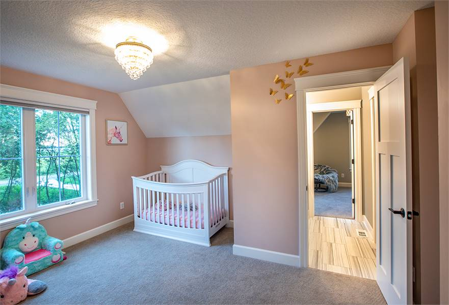 Nursery room with light pink walls and a vaulted ceiling mounted with a warm semi-flush light.
