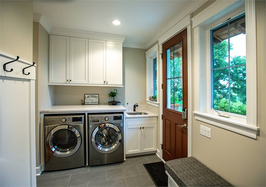 The laundry room is equipped with front-load appliances, white cabinets, and an undermount sink.