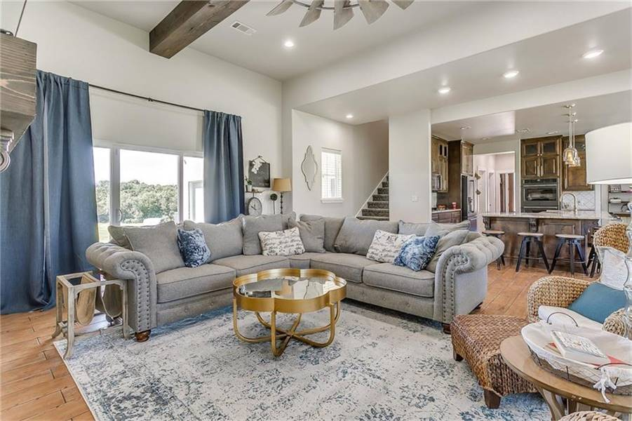 Across the kitchen is the family room with a tufted V-shaped sectional, glass top coffee table, and a wicker lounger over a distressed area rug.