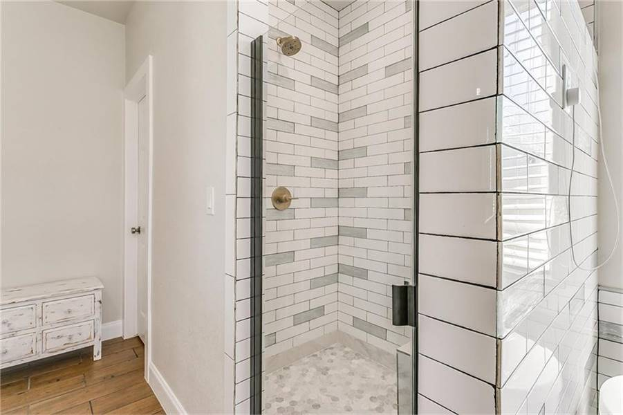 A closeup view of the walk-in shower with hex tile flooring and white brick walls mounted with brass fixtures.