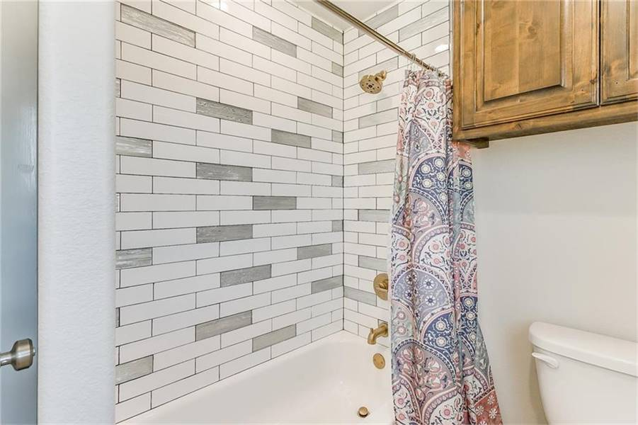 The shower and tub combo next to the toilet is complemented with brass fixtures and a lovely printed curtain that serves as its door.
