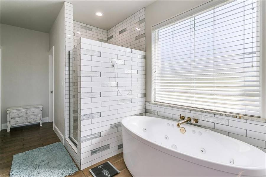A gray shaggy rug over the hardwood flooring complements the shower area that's placed next to the whirlpool tub.