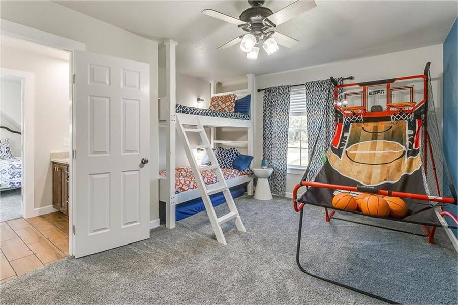 This bedroom is filled with a white bunk bed, basketball rings, and a traditional ceiling fan.
