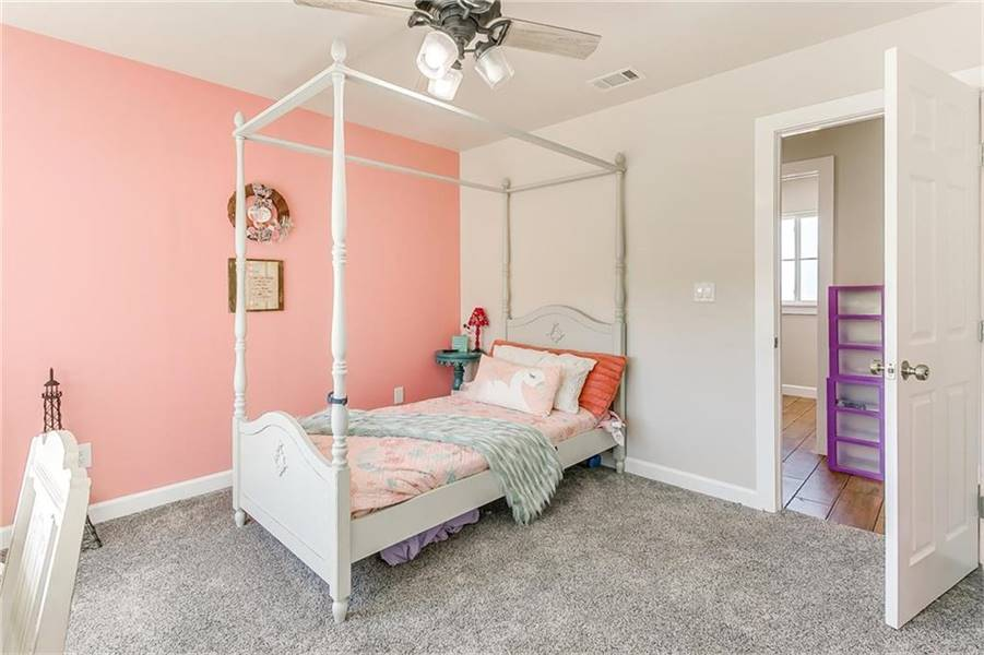 Kid's bedroom with dual-tone walls and a canopy bed sitting on a gray carpet flooring.