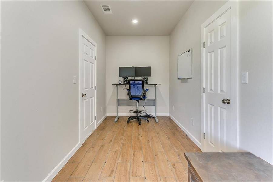 The home office has a sleek desk and a blue swivel chair sitting on a wide plank flooring.