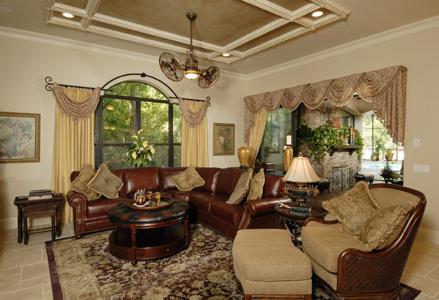 The living room has brown leather seats and a round ottoman that sits on a floral area rug.