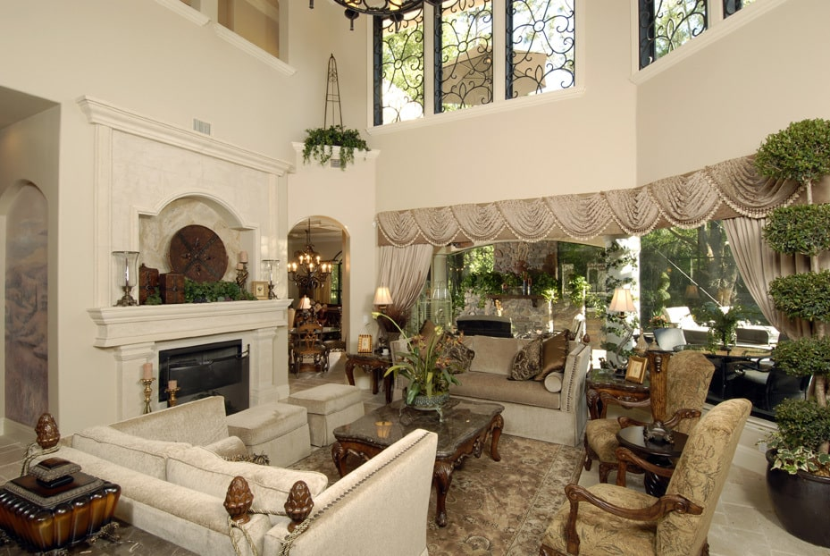 The family room features a fireplace and massive windows dressed in classy valances and draperies.
