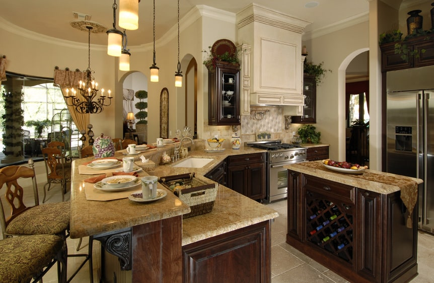 Kitchen with a two-tier peninsula, dark wood cabinets, and a granite top island fitted with crisscross wine rack.