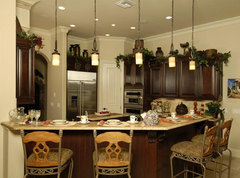 Faux plants, antique vases, and warm glass pendant lights adorn the kitchen.