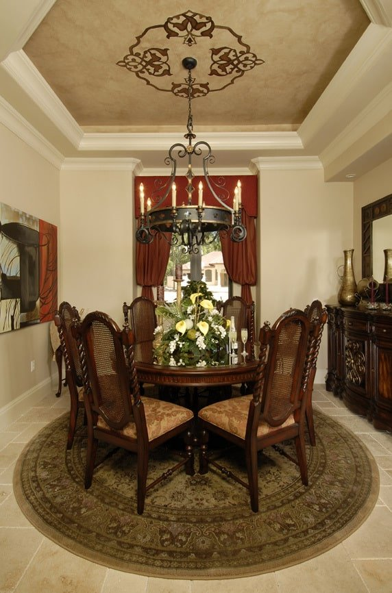 The formal dining room offers cushioned chairs, a round dining table, and a wrought iron chandelier that hangs from the beautiful tray ceiling.