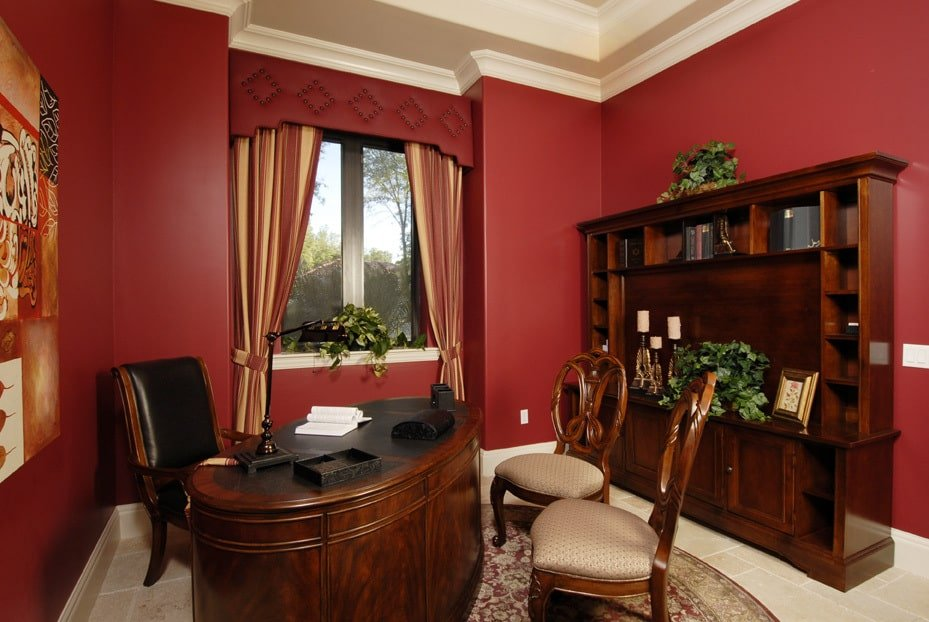 The study has red walls, dark wood furnishings, and a limestone flooring topped with a round area rug.