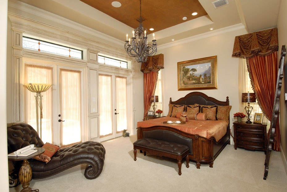 Master bedroom with a cozy bed, a leather tufted chaise lounge, and two sets of french doors that leads out to the pool deck.
