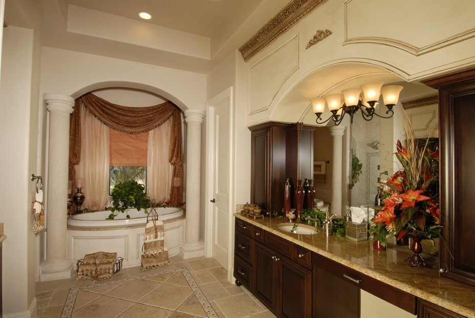 The master bathroom is equipped with immense sink vanity and an opulent tub lined with marble columns.