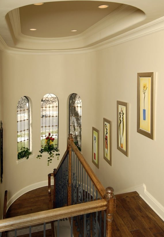 Wooden staircase fixed against the beige walls that are mounted with arched windows and gorgeous artworks.