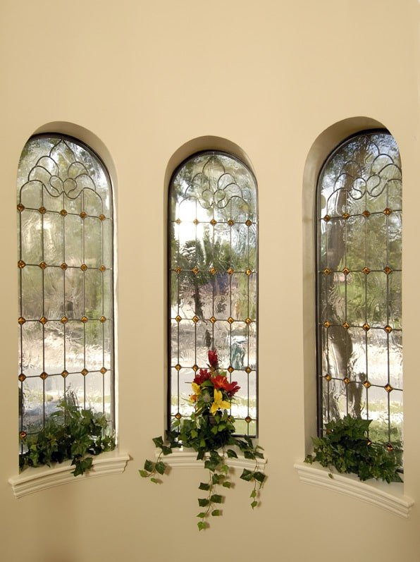 A closer look at the arched windows adorned with intricate details and green plants.