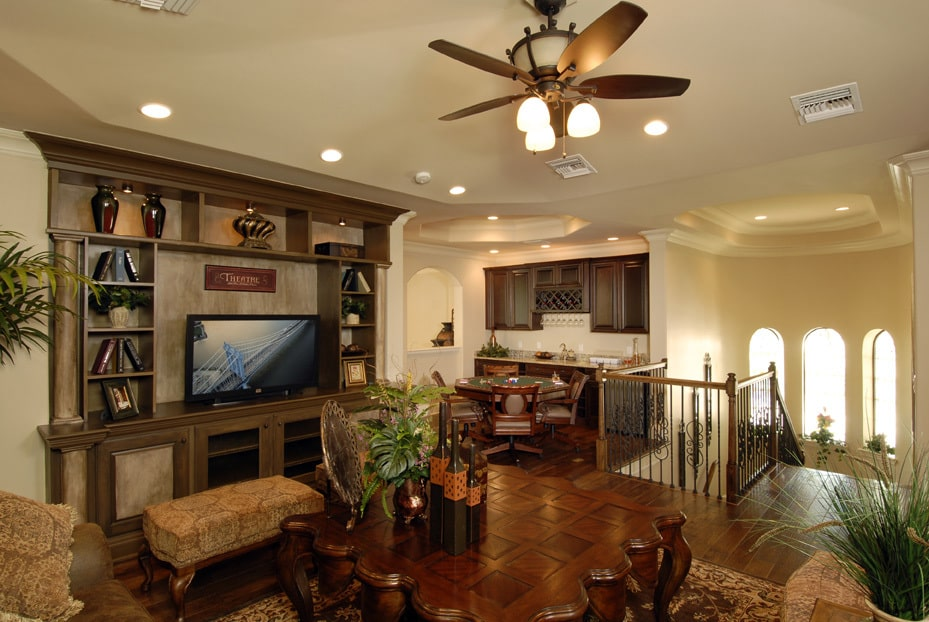 A spacious loft filled with cozy seats, a game table, and a wet bar.