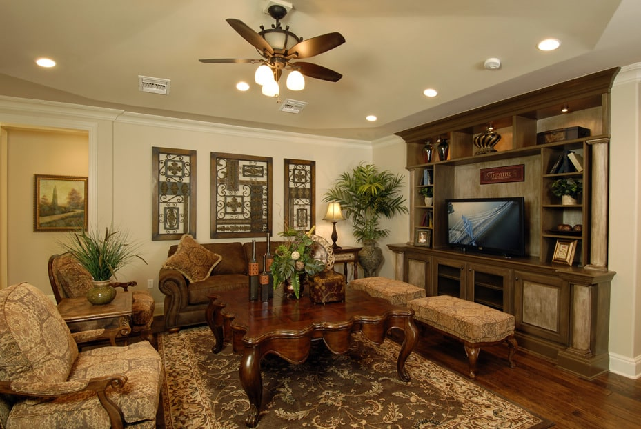 The upper living has cushioned chairs, a large coffee table, and a TV sitting on top of the wooden cabinet.