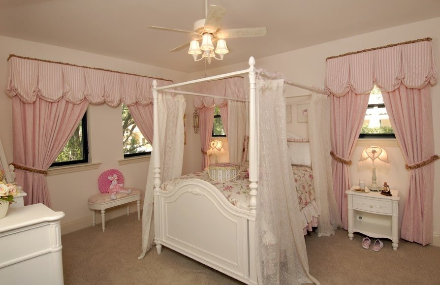Kid's bedroom with white furnishings, beige carpet flooring, and glazed windows covered in pink curtains.