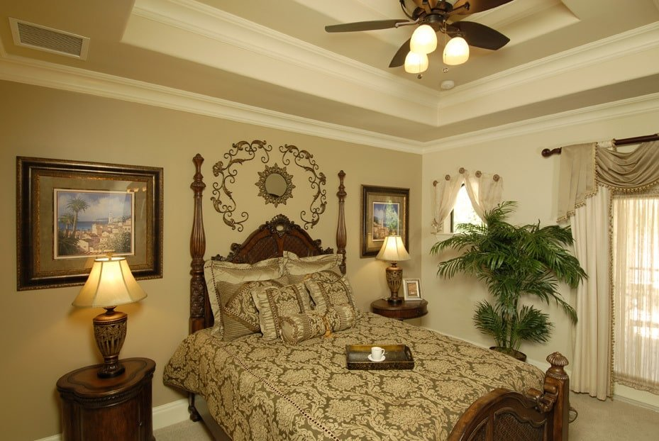 This bedroom has a step ceiling, dark wood furniture, and beige walls lined with white moldings.