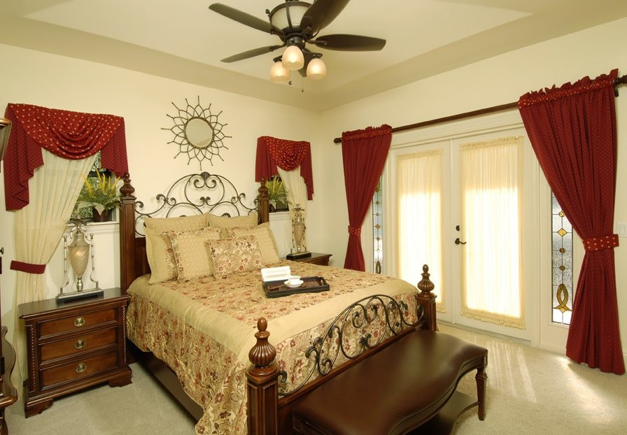 Another bedroom showcasing an ornate bed flanked by wooden nightstands and classy table lamps.