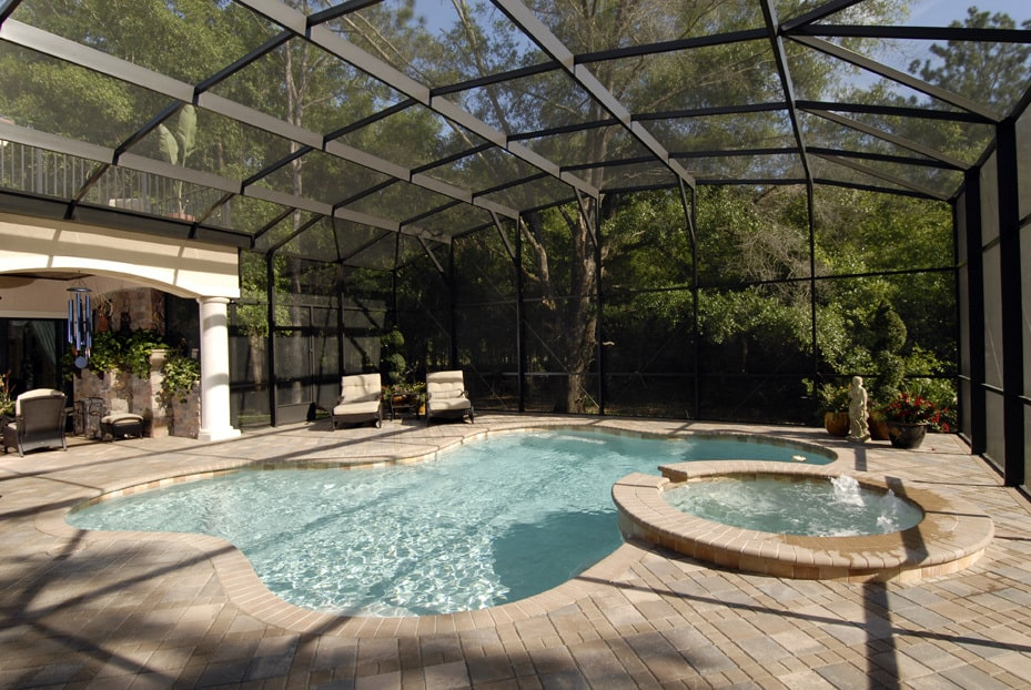A farther look of the pool showing the integrated spa and cushioned loungers over the tiled pavement.